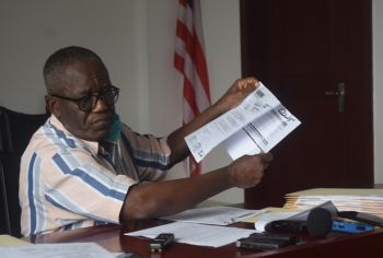 Prof. Tarpeh displays financial documents
